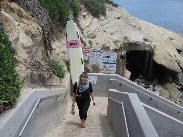A lady climbs stairs up from the beach, past a lifeguard's rescue board.