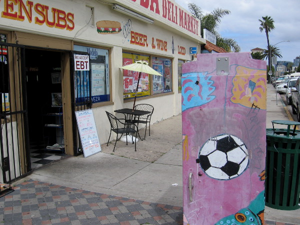 A soccer ball on utility box by a small local market known for their sub sandwiches.