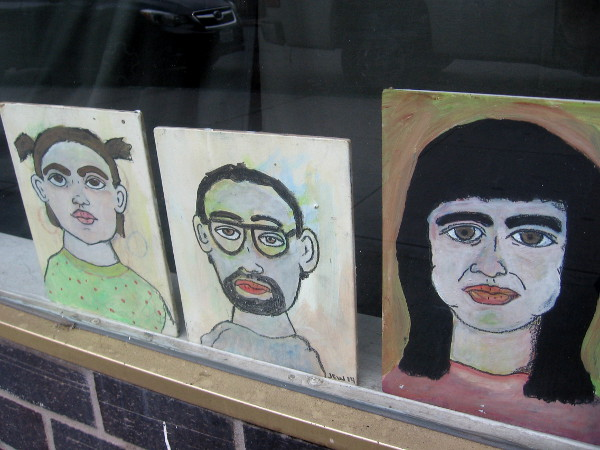 Several faces line the bottom of a closed shop window.