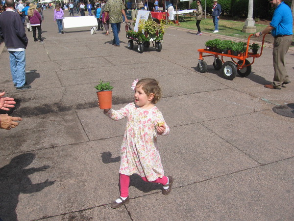 Child gives potted plant to spectator during floral wagon parade in Balboa Park.