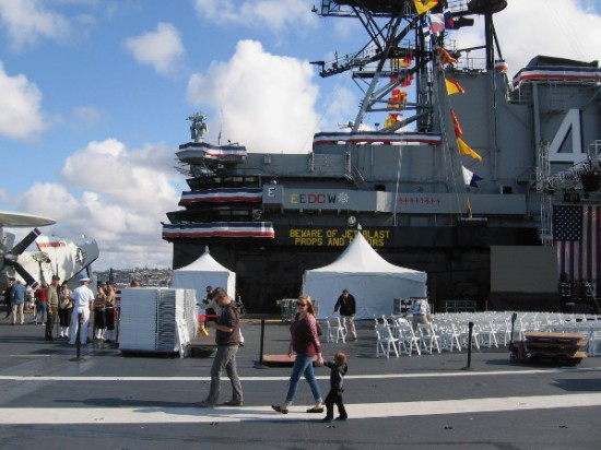 People cross flight deck of USS Midway aircraft carrier museum to attend a special Memorial Day weekend event. Chairs are for a Wynonna Judd Judd performance later this evening.