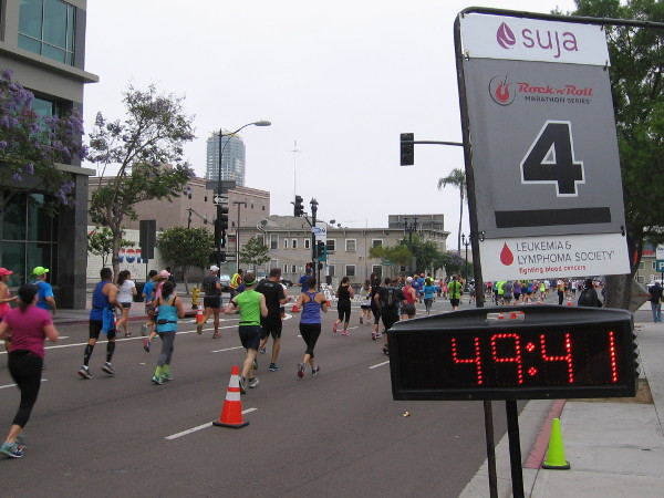 Marathon participants at the mile 4 marker, racing through downtown San Diego.