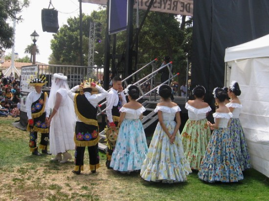 A competing dance troupe wearing colorful costumes waits at the edge of Old Town's historic plaza.