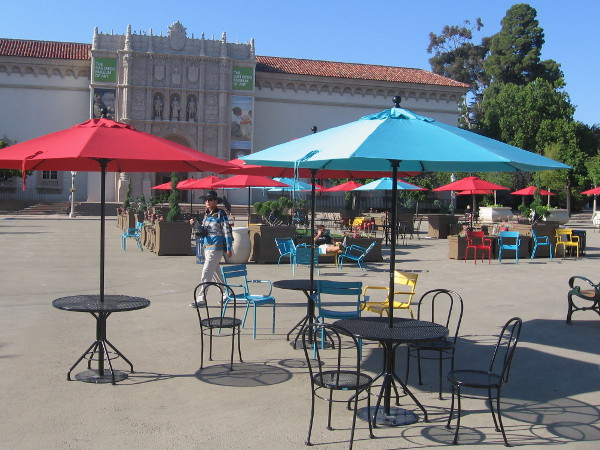 People mix with red and blue umbrellas in the big square in front of the San Diego Museum of Art.