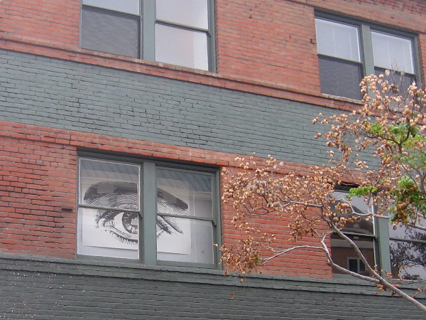 Gigantic eye stares out window at me as I continue to walk south down Seventh Avenue.