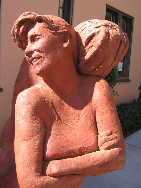 Light shines on Sisterhood terracotta sculpture, by artist Mary Buckman.