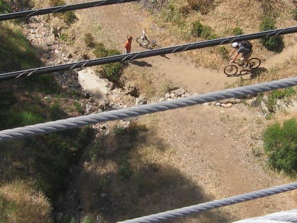 Bicyclists enjoy a dirt trail 70 feet below.