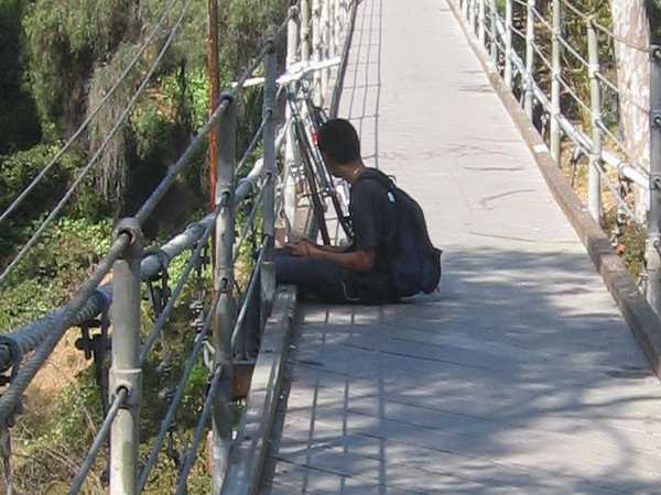 Boy sits thoughtfully on the Spruce Street suspension bridge in Bankers Hill.