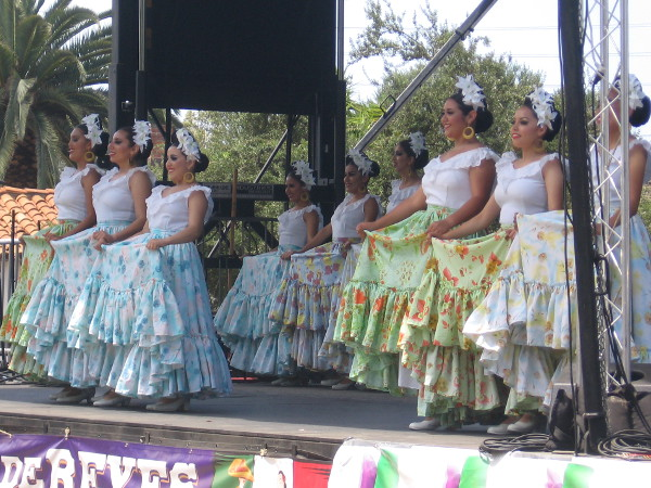 With flowers in their hair, bright dresses and broad smiles, these dancers bring cheers and whoops from the crowd.