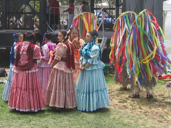 Long colored ribbons stream from very odd costumes. The headpieces appear to be religious icons or altars.