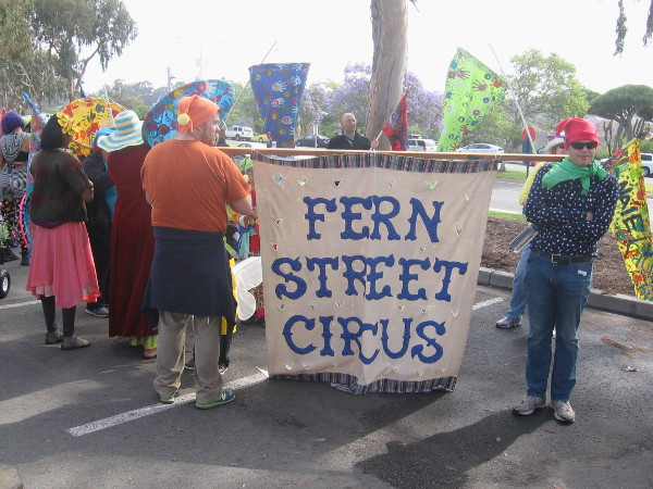 San Diego's own Fern Street Circus has gathered for the parade holding colorful banners.