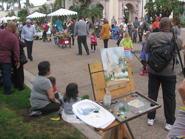 A painter in Balboa Park gets an eyeful as the parade passes by.