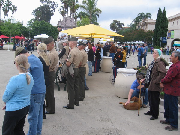Civilian and military bystanders look on as a memorable San Diego event is taking place.