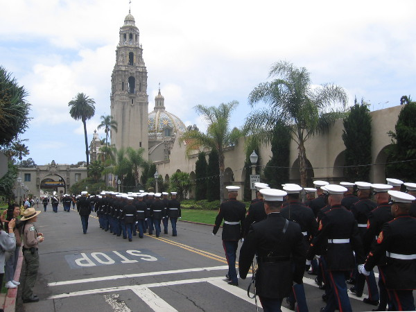 Proudly marching Marines head west down El Prado toward California Tower and Museum of Man.