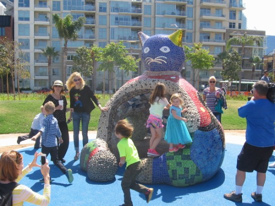 Kids play on a newly installed fat hollow Cat. The interactive sculpture sits next to the playground in San Diego's super cool, one-year-old waterfront park!
