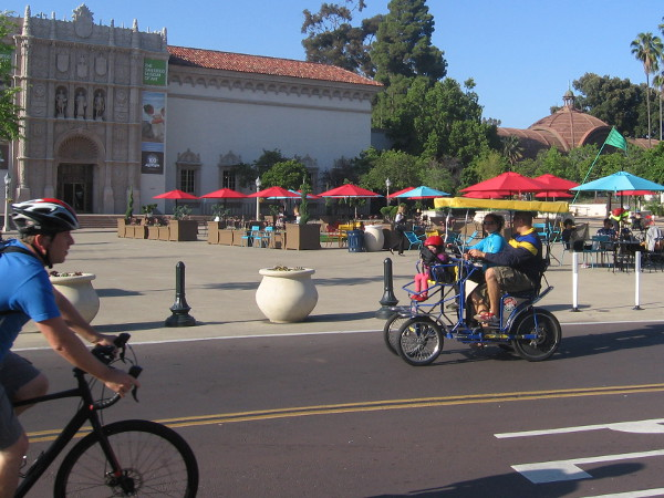 Bicyclist and tourists on a rented quadracycle head through the beautified Plaza de Panama.