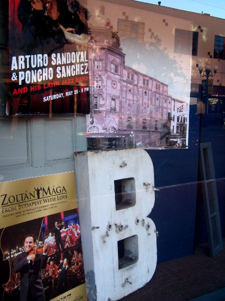Old photo and letter B from Balboa Theatre sign on display by sidewalk next to Horton Plaza.