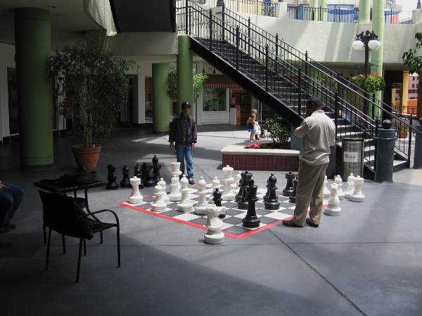 People enjoy a leisurely game of chess with gigantic chessboard and pieces at Horton Plaza.