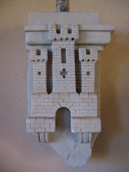 Castle, on left side of the base of Serra Memorial, depicts the heraldic emblem of the former Spanish Kingdom of Castile.