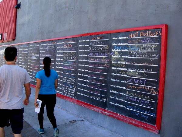 People walk down a Hillcrest sidewalk past chalk street art desires.