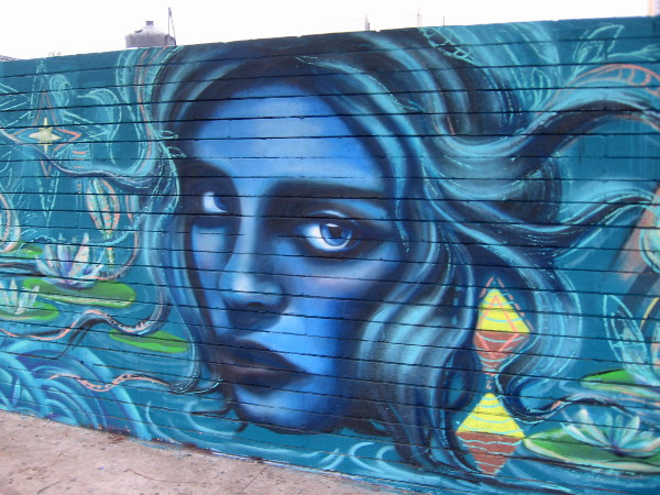 Large blue female face looks out from SILO wall at passing traffic on F Street.