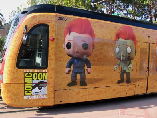 A new San Diego Comic-Con trolley wrap features Conan O'Brien turned into what appear to be Funko POP! toy figures. Here he's a blank-eyed zombie, and his own ordinary bland self.