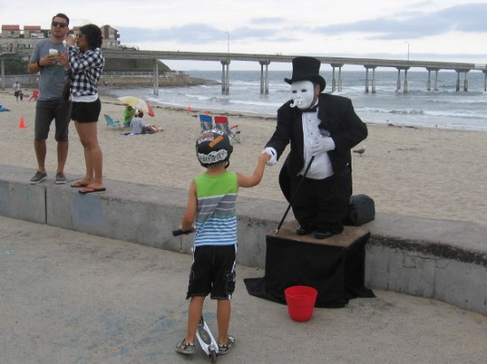 A masked street performer shakes hands with a kid on a scooter. The Ocean Beach Municipal Pier stretches in the background.