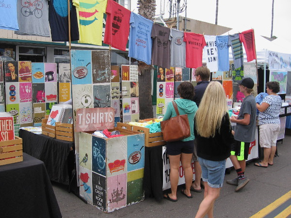 San Diegans and Obetians check out a street vendor selling colorful t-shirts.
