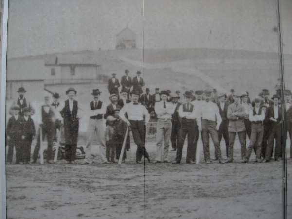 First panel of photo mural shows baseball teams from San Diego and Coronado in 1874. Ball field is on the block bounded by Sixth, C Street, Seventh and Broadway.