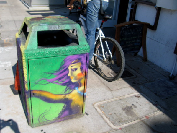 Bicyclist in Hillcrest rides down the sidewalk past another great example of trashcan art.