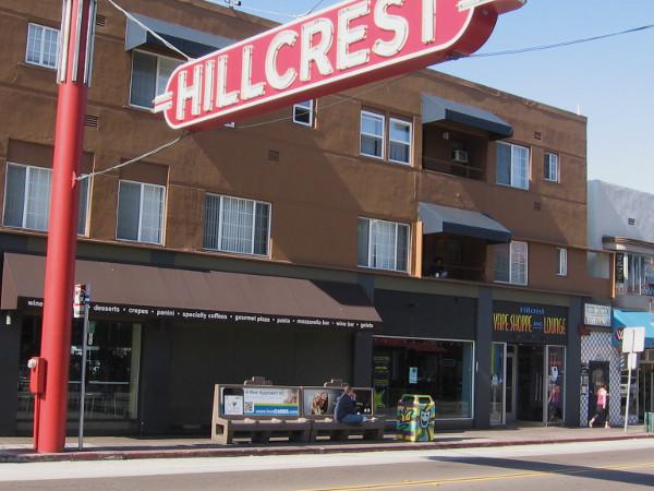 An artistic trashcan waits by a bus stop near the Hillcrest landmark sign.
