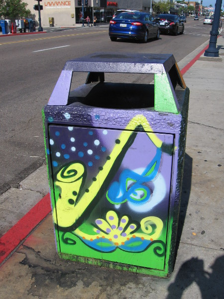 A big, joyful saxophone has been painted on this trashcan.