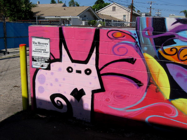 Pink abstract cat awaits at edge of Hillcrest alley.