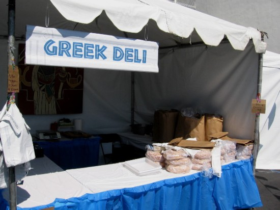 Pita bread is stacked up waiting at one end of this Greek Deli tent.