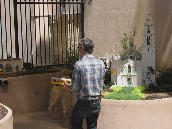 Volunteer at San Diego Model Railroad Museum walks past 3D-printed model of the historic California Building with its bell tower.