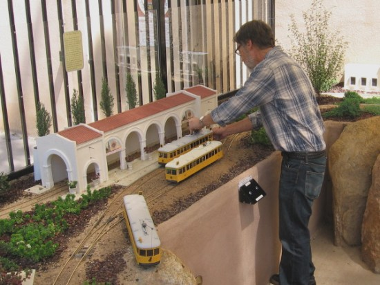 Putting a model of a streetcar on the tracks. A hundred years ago, John D. Spreckels' Class 1 streetcars provided transportation around San Diego.