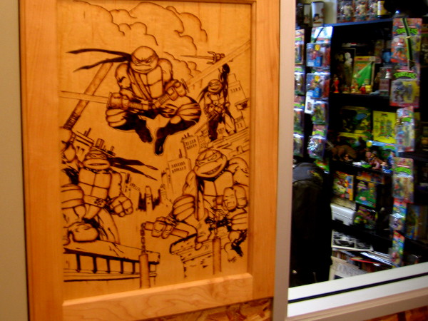 Wood panel by studio window shows the four funny, dynamic turtles in action.
