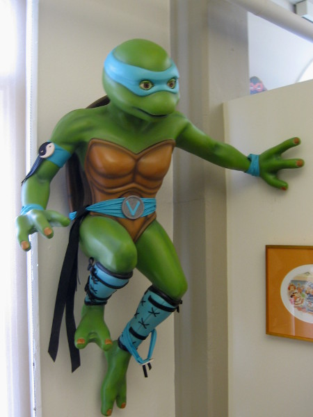 Leonardo, wearing a blue mask, overlooks visitors to a room where kids and adults are encouraged to draw, experience and read about comic art.