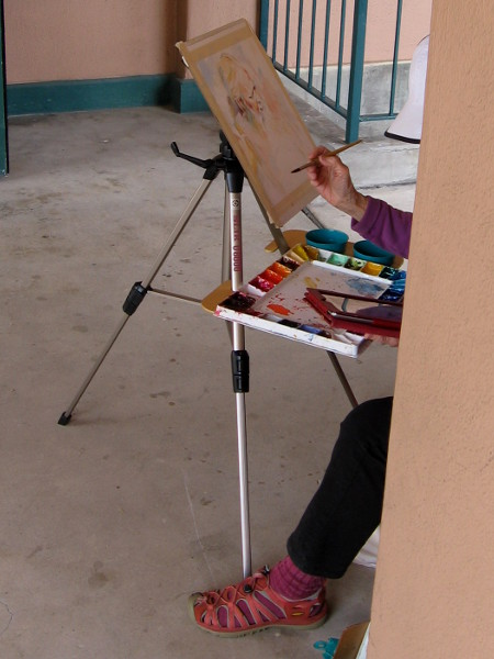 Artist in a corner of NTC Liberty Station creates a watercolor portrait.