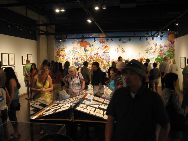 Visitors check out original comic book art created for Comic-Con souvenir program books over the past 45 years.