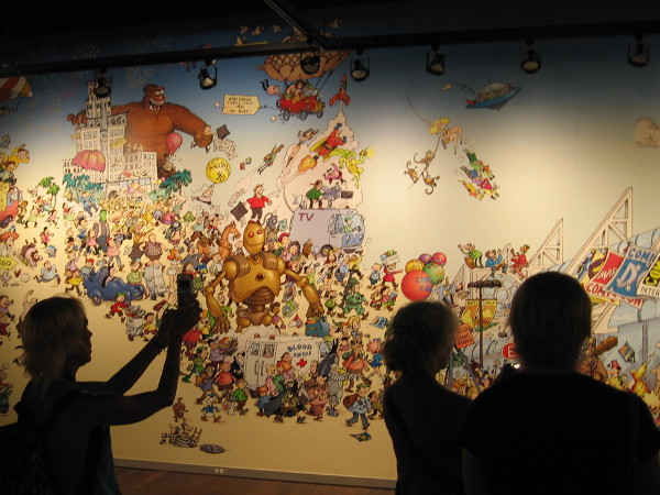 Visitors to the San Diego's Art of Comic-Con museum exhibit enjoy a huge mural from a 2008 book cover created by legendary cartoonist Sergio Aragones.