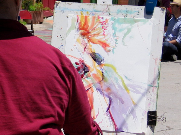 A local artist from Spanish Village in Balboa Park streaks color across a canvas. A skilled hand and eye produces the same bold living essence expressed by the dance.