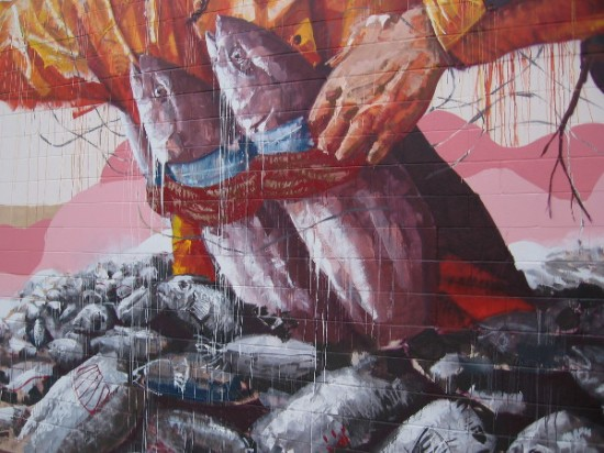 A tuna fisherman's hand and his bound, bloody catch emerge from a pile of fish.