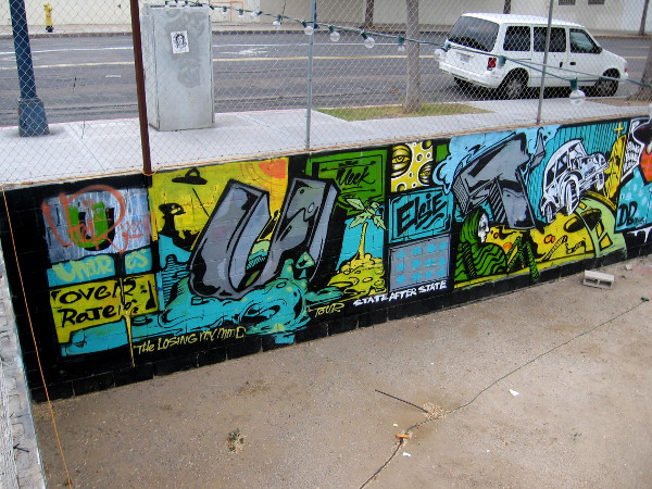 Super colorful artwork jammed onto this low wall almost appears like panels in a comic book or graphic novel.