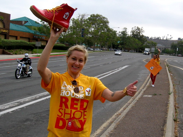 Volunteer at a Mission Valley intersection lifts a red shoe and gives a thumbs up! She was raising money for Ronald McDonald House today!