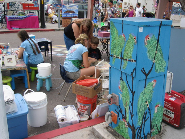Young artists use their imaginations as they work behind a utility box decorated with parrots in Ocean Beach.