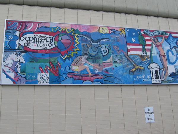 Public art mural on one wall depicts the annual Ocean Beach Street Fair and Chili Cook-Off.