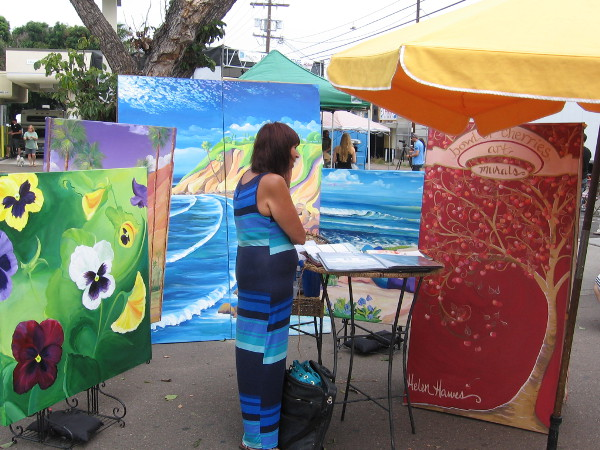 Someone checks out large works of colorful art in OB.