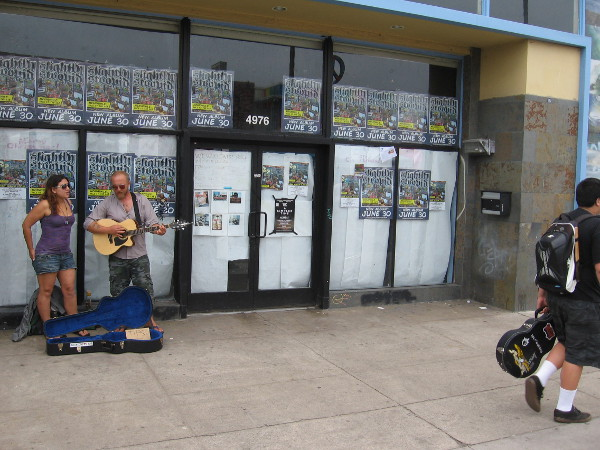 Street musicians in OB next to a storefront on a summer day.
