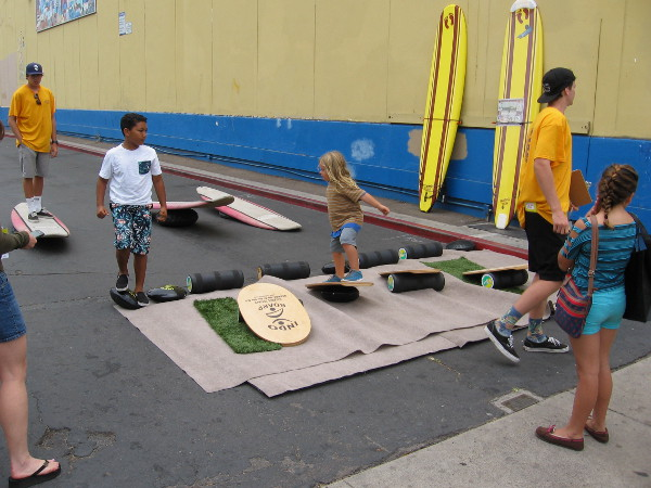 Young and old were practicing maintaining balance on a board that mimics surfing.